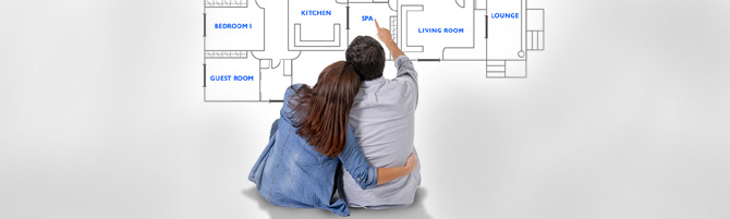 Young attractive couple in love happy together planning and pointing blueprints floor plan and design of new house home flat or apartment in real state concept